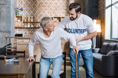 Careful attentive volunteer helping a senior man to stand up. Support. Young reliable social worker looking attentive and careful while helping an old men to Royalty Free Stock Image