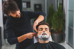 Careful barber serving his client Stock Photography