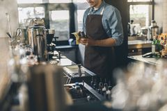 Careful bartender is cleaning shaker with washcloth. Close up of a smiling young bartender standing at his workplace with a cocktail shaker and cleaning it royalty free stock photography