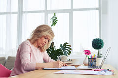 Careful blonde drinking coffee while writing Royalty Free Stock Photos