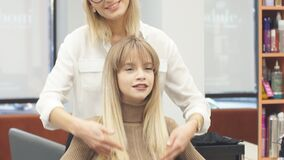 Careful hairdresser holding client's hair in hands. Careful caucasian hairdresser holding client's hair in hands, going to cut off tips of hair, making hairdo to stock video footage