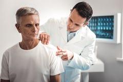 Careful dark-haired doctor examining shoulder stock photos