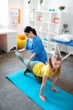 Careful dark-haired physical therapist holding leg of training girl. Leaning on mat. Careful dark-haired physical therapist holding leg of training girl while royalty free stock photo