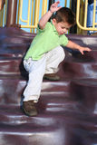 Careful Descent. Young boy balancing as he descends playground equipment royalty free stock photography