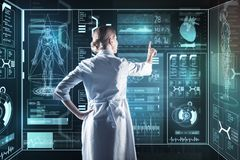 Careful doctor touching a futuristic computer while working. Medical innovation. Calm smart enthusiastic doctor using amazing futuristic technologies while stock photo