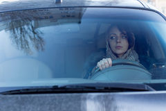 Careful female driver. View through the windscreen of a careful female driver checking for traffic in her rear view mirror and maintaining an awareness of her stock image