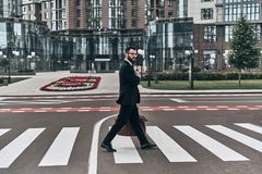 Always careful. Full length of young man in full suit crossing the street while walking outdoors stock image