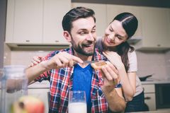 Careful girl stands behind guy and loks at him. She smiles. Man puts some chocolate paste on toast and look at her. He. Smiles as well. They are happy royalty free stock images