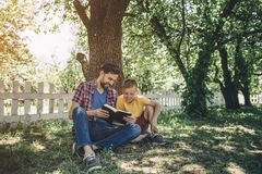 Careful an good father is sitting with his son inder tree and holding book. They are looking at it. They are reading it. Boy is very interested. He looks happy stock photography