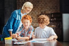 Careful grandma watching her grandsons painting together Stock Images