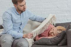 Careful grown son covering sleeping mother on sofa. With blanket royalty free stock photos