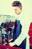 Careful male employee using machine to bottle wine. At sparkling wine factory Royalty Free Stock Photography