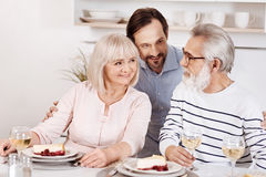 Careful mature son enjoying family dinner with parents at home. Expressing love to my parents. Happy delighted mindful men having dinner and enjoying time with Royalty Free Stock Images
