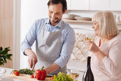 Careful mature son helping aged mother in the kitchen. Cooking for my mother. Cheerful smiling mature son standing in the kitchen and cooking vegetarian salad Royalty Free Stock Photography