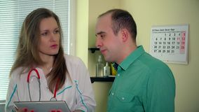Careful medic woman showing sad patient man test results on digital tablet stock footage