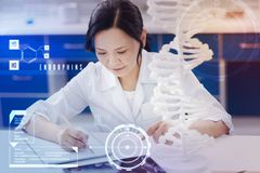 Careful medical worker making notes while analyzing the DNA structure. Making important notes. Calm attentive medical worker sitting in front of the DNA model stock photo