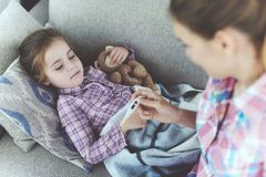 Careful Mother Checking Sick Child Temperature. Attentive Woman Sits Near Ill Little Daughter. Pretty Girl has Cold and Fever Lying on Sofa under Blanket or stock photography