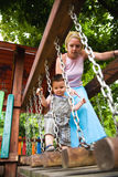 Careful mother helping son. Careful mother helping her son, walking on a wooden structure in playground royalty free stock photo