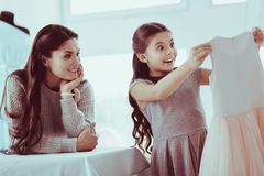 Careful mother presenting her daughter a dress stock photography