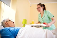Careful nurse service a breakfasr to od patient. At nursing home royalty free stock image