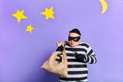 Careful prisoner with a sack trying to hide from police royalty free stock images