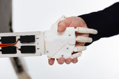 Careful progressive man shaking hands with a robot Royalty Free Stock Photography