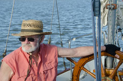Careful Sailing. A senior man at the helm of sailboat navigates on Fern Ridge Reservoir near Eugene, Oregon Stock Image