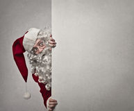Careful Santa Claus. Santa Claus appears from behind a white wall Royalty Free Stock Image