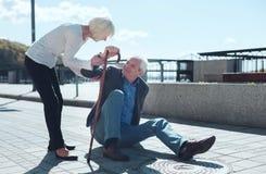 Careful senior wife taking care of husband falling dawn Royalty Free Stock Images