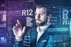 Careful specialist looking serious while checking important information. Important information. Calm attentive smart programmer thoughtfully looking at the Royalty Free Stock Photos