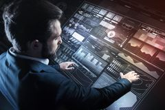 Careful specialist putting hands on the transparent screen while working alone. Convenient screen. Calm serious responsible programmer looking careful while Stock Photos