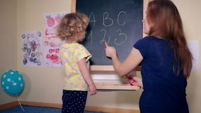 Careful teacher woman teaching smart child girl letters and numbers stock video footage