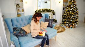 Careful wife neatly and with trepidation draws New Year`s gift for beloved husband, sitting on blue sofa in festively. Beautiful woman wraps holiday surprise for stock footage