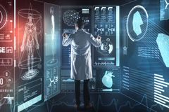 Calm medical worker feeling concentrated while touching the transparent screen. Careful worker. Attentive young medical worker carefully touching the futuristic stock image