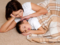 Careful young mum near to the sleeping small son Stock Photography