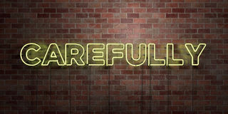 CAREFULLY - fluorescent Neon tube Sign on brickwork - Front view - 3D rendered royalty free stock picture Stock Photography