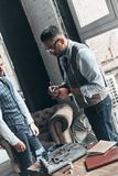 Carefully noting. Two young fashionable men having a discussion while standing in workshop stock image