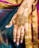 Completed Mehndi design displayed on hand and fingers of Indian wedding guest. Carefully painted intricate design using henna, Mehndi art, on the hand of young stock photography