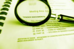 Carefully Studying tender documents. A photograph showing a magnifying glass used to focus upon the words tender documents, in a commercial business contract Royalty Free Stock Images