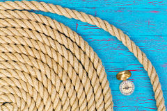Carefully wound rope with compass over blue Royalty Free Stock Photography
