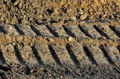 Careggiate nel fango, bulldozer di orme del dettaglio nella strada della costruzione Fotografie Stock Libere da Diritti