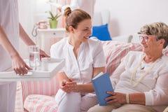 Caregiver με τα φάρμακα για τον ηλικιωμένο ασθενή στοκ φωτογραφίες