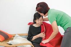 Caregiver που βάζει το κάλυμμα στην ηλικιωμένη γυναίκα στοκ εικόνες