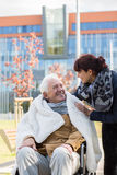 Caregiver caring about disabled man Royalty Free Stock Image
