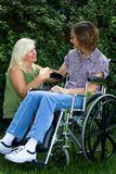 Caregiver Comforter. Caregiver tries to comfort an elderly disabled women in a wheelchair Stock Photo