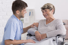 Caregiver comforting elderly woman. Professional caregiver comforting smiling elderly women on wheelchair Royalty Free Stock Photos