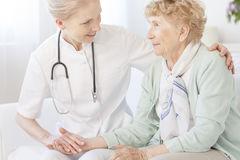 Caregiver is comforting an older lady Stock Images