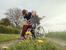 Caregiver comforts worried senior woman with wheelchair stock photography