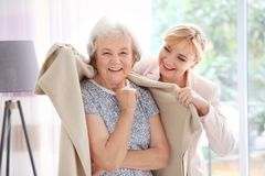 Caregiver covering senior woman with plaid. Caregiver covering senior women with plaid at home royalty free stock photography