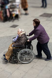 Caregiver and disabled lady. Disability. A caregiver brings a disabled lady in wheelchair (Barcelona, Spain Royalty Free Stock Photos